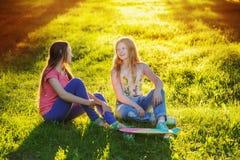 Muchachas adolescentes con con el monopatín en parque del verano Foto de archivo