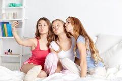 Muchachas adolescentes con el smartphone que toma el selfie en casa Fotografía de archivo libre de regalías