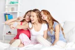 Muchachas adolescentes con el smartphone que toma el selfie en casa Imagen de archivo