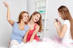 Muchachas adolescentes con el smartphone que toma la imagen en casa Foto de archivo libre de regalías