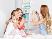 Muchachas adolescentes con el smartphone que toma la imagen en casa Fotos de archivo libres de regalías