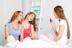 Muchachas adolescentes con el smartphone que toma la imagen en casa Fotografía de archivo libre de regalías