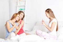 Muchachas adolescentes con el smartphone que toma la imagen en casa Foto de archivo