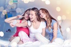 Muchachas adolescentes con el smartphone que toma el selfie en casa Fotografía de archivo