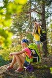 Muchachas adolescentes con la mochila que descansa en viaje del bosque y concepto del turismo Imagen de archivo