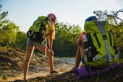 Muchachas adolescentes con la mochila que descansa en viaje del bosque y concepto del turismo Foto de archivo libre de regalías