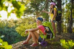 Muchachas adolescentes con la mochila que descansa en viaje del bosque y concepto del turismo Fotos de archivo