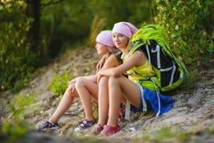 Muchachas adolescentes con la mochila que descansa sobre la arena Concepto del recorrido y del turismo Imagen de archivo libre de regalías