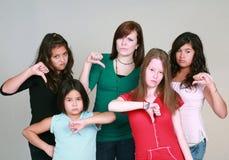 Muchachas adolescentes con los pulgares abajo Imagen de archivo libre de regalías