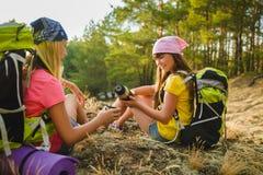 Muchachas adolescentes con té de la reclinación y de la bebida de la mochila Concepto del recorrido y del turismo Fotografía de archivo libre de regalías