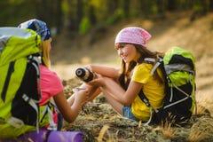 Muchachas adolescentes con té de la reclinación y de la bebida de la mochila Concepto del recorrido y del turismo Fotos de archivo
