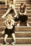 Muchachas adolescentes de la moda feliz que se sientan en pasos Foto de archivo
