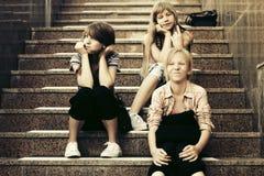 Muchachas adolescentes de la moda feliz que se sientan en pasos Fotografía de archivo libre de regalías