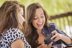 Muchachas adolescentes de la raza mixta que trabajan en los dispositivos electrónicos Foto de archivo