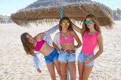 Muchachas adolescentes de los mejores amigos debajo del paraguas de la paja Fotografía de archivo libre de regalías