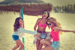Muchachas adolescentes de los mejores amigos debajo del paraguas de la paja Fotografía de archivo