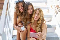 Muchachas adolescentes de los mejores amigos en fila con smartphone Foto de archivo