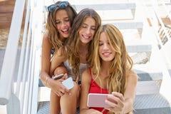 Muchachas adolescentes de los mejores amigos en fila con smartphone Imágenes de archivo libres de regalías
