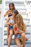 Muchachas adolescentes de los mejores amigos en fila con smartphone Fotografía de archivo