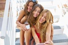 Muchachas adolescentes de los mejores amigos en fila con smartphone Imagenes de archivo