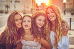 Muchachas adolescentes de los mejores amigos en la puesta del sol en la ciudad Foto de archivo libre de regalías
