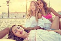 Muchachas adolescentes de los mejores amigos junto en puesta del sol de la playa Foto de archivo