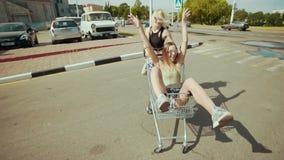 Muchachas adolescentes del inconformista joven que tienen montar a caballo de la diversión en carro de la compra en el estacionam metrajes