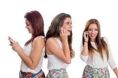 Muchachas adolescentes del Threesome que hablan en los teléfonos elegantes Imagen de archivo libre de regalías
