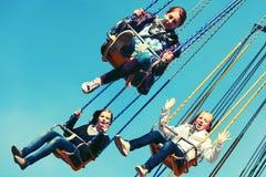 Muchachas adolescentes en el carrusel de cadena del oscilación Foto de archivo libre de regalías