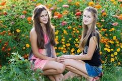 Muchachas adolescentes en el fondo de flores Fotografía de archivo libre de regalías