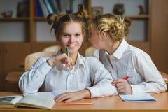 Muchachas adolescentes en la biblioteca escolar o la sala de clase, discutiendo lo que están aprendiendo Imagen de archivo libre de regalías