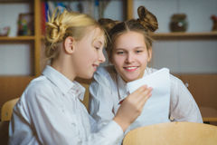 Muchachas adolescentes en la biblioteca escolar o la sala de clase, discutiendo lo que están aprendiendo Fotos de archivo libres de regalías