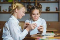 Muchachas adolescentes en la biblioteca escolar o la sala de clase, discutiendo lo que están aprendiendo Imágenes de archivo libres de regalías