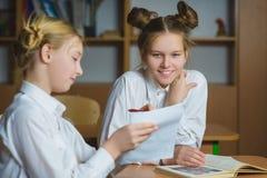 Muchachas adolescentes en la biblioteca escolar o la sala de clase, discutiendo lo que están aprendiendo Foto de archivo libre de regalías