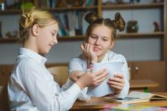 Muchachas adolescentes en la biblioteca escolar o la sala de clase, discutiendo lo que están aprendiendo Foto de archivo