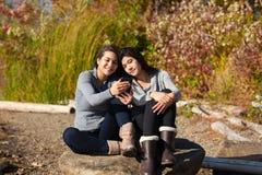 Muchachas adolescentes en roca usando smartphone por el lago en otoño Imagen de archivo