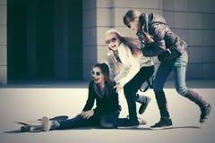 Muchachas adolescentes felices con el monopatín en calle de la ciudad Foto de archivo