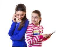 Muchachas adolescentes felices con la tableta y el smartphone digitales Foto de archivo libre de regalías