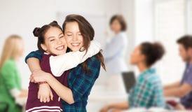 Muchachas adolescentes felices del estudiante que abrazan en la escuela Imagenes de archivo