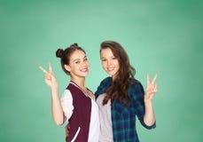 Muchachas adolescentes felices del estudiante que muestran el signo de la paz Imagen de archivo