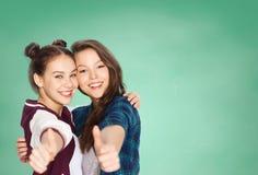 Muchachas adolescentes felices del estudiante que muestran los pulgares para arriba Fotos de archivo