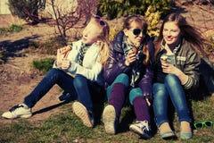 Muchachas adolescentes felices que comen un helado al aire libre Imágenes de archivo libres de regalías