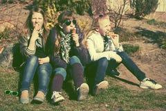 Muchachas adolescentes felices que comen un helado al aire libre Fotografía de archivo libre de regalías