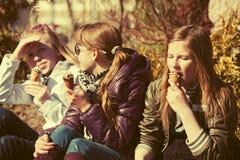Muchachas adolescentes felices que comen un helado al aire libre Imagen de archivo libre de regalías