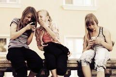 Muchachas adolescentes felices que invitan a los teléfonos celulares Imagenes de archivo