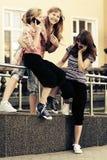 Muchachas adolescentes felices que invitan a los teléfonos celulares en calle de la ciudad Imagen de archivo