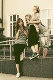 Muchachas adolescentes felices que invitan a los teléfonos móviles contra una construcción de escuelas Imágenes de archivo libres de regalías