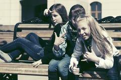 Muchachas adolescentes felices que se sientan en banco en una calle de la ciudad Foto de archivo libre de regalías