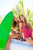 Muchachas adolescentes locas felices de la persona que practica surf que sonríen en el coche Foto de archivo libre de regalías