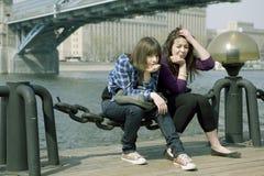 Muchachas adolescentes pensativas que se sientan en el río Fotografía de archivo libre de regalías